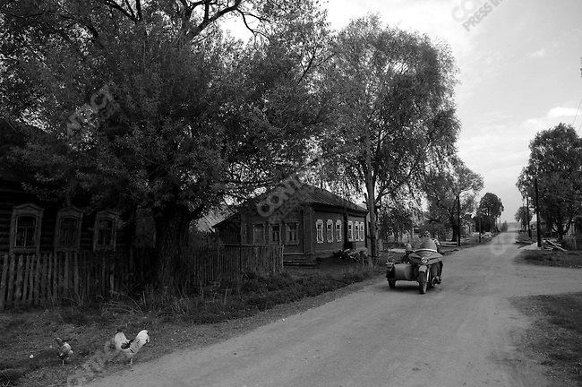 Three men on a motocycle and sidecar drove through the quiet village of Belkovo in Ryazansk region. Russia, May 6, 2008.