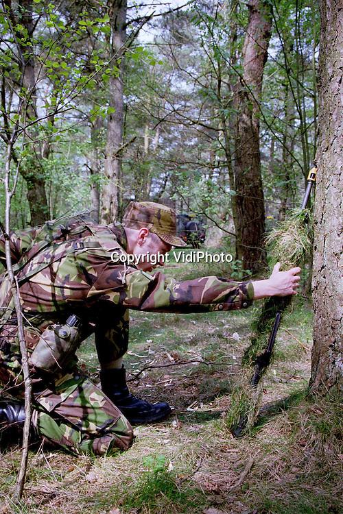 Foto: VidiPhoto..GARDEREN - De 132e Verbindingscompagnie van de Generaal Kootkazerne startte maandag met een vierdaagse NBC-oefening in de bossen bij Garderen. NBC staat voor Nucleair, Biologisch en Chemisch. De .oefening heeft niets van doen met mogelijke uitzending naar Kosovo, maar was al eerder gepland. De militairen beginnen met een camouflage- en  .beveiligingsoefening. Daarna moeten ze zich verplaatsen met extra beschermende kleding aan en een gasmasker op, een warme klus de .komende dagen.