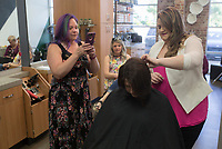 """NWA Democrat-Gazette/CHARLIE KAIJO Kasey Coonrod of Bentonville (right) works on the hair of Anna Sarratt as Rose Birdsong of Fayetteville takes a picture (left) during a formal hair class, Monday, May 13, 2019 at Sola Salons in Bentonville.<br /><br />""""A lot of stylists are new to this industry or want more confidence in this area and the best way is through education,"""" Kasey Coonrod said of her reason to have the class. """"Some stylists are intimidated by weddings and formal events."""""""
