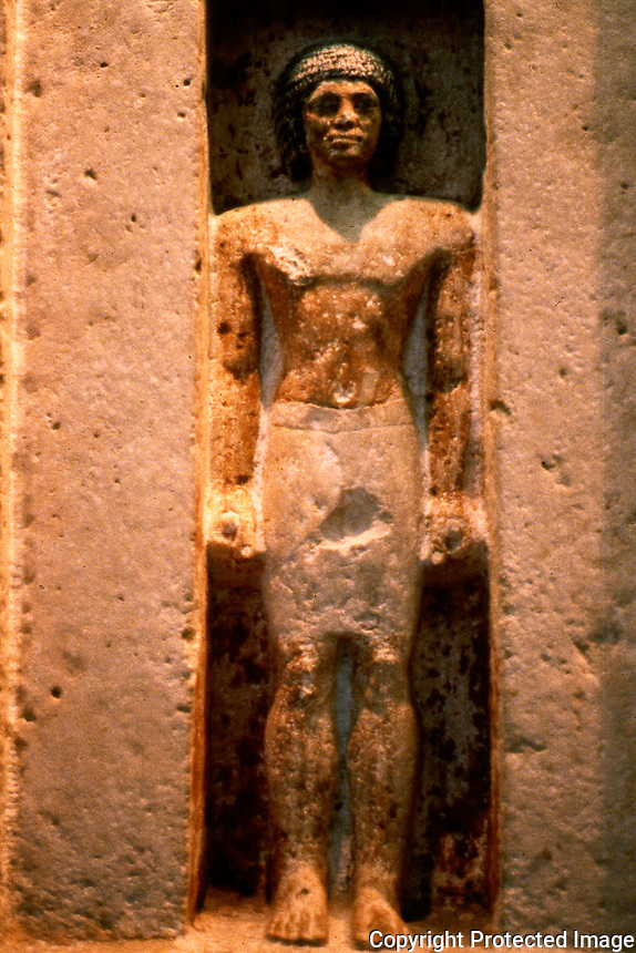 Egypt:  Butet I, 5th Dynasty, 2400 B.C.  Limestone figurine in a niche of a false door;  he is emerging from the burial chamber into the chapel to receive his food offering.   British Museum.