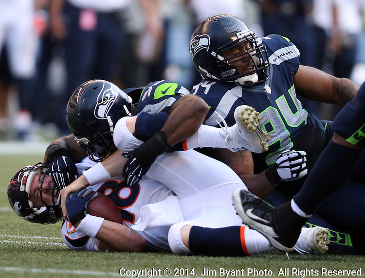 Denver Broncos quarterback Peyton Manning is sacked by Seattle Seahawks defensive end O'Brien Schofield (93) and defensive tackle    Kevin Williams  (94) in the fourth quarter at CenturyLink Field in Seattle, Washington on September 21, 2014. The Seahawks won 26-20 in overtime.    ©2014. Jim Bryant Photo. All rights Reserved.