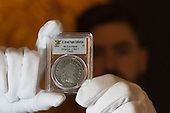London, UK. 13 March 2015. Pictured: A Sotheby's employee presents the most famous United States coin, the 1804 Silver Dollar, estimate: USD 8-10 million. Sotheby's and Stack's Bowers Galleries will present the D. Brent Pogue Collection of masterpieces of United States coinage - the most valuable coin collection in private hands - across a series of seven auctions beginning 19 May 2015 at Sotheby's New York headquarters. The overall collection, which consists of more than 650 individual coins, is expected to achieve well in excess of USD 200 million - more than any other series of rare coin auctions in history. Photo: Bettina Strenske