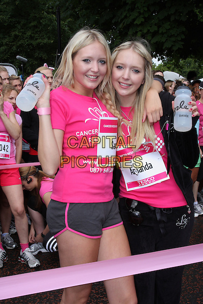 SAMANDA - SAMANTHA & AMANDA MARCHANT.Cancer Research Race For Life Charity 5k Run at Hyde Park, London, England..July 19th 2009.half length sam twins sisters siblings  family pink t-shirt black shorts tracksuit drink water arm over shoulder bottle braid plait .CAP/ROS.©Steve Ross/Capital Pictures.
