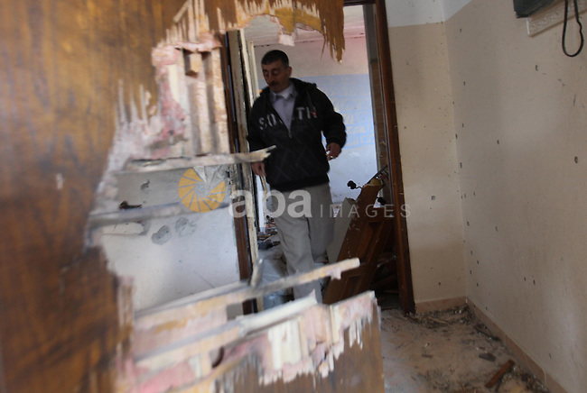 A Palestinian man checks the damage inside a house after three Palestinians were killed during Israeli operations in the West Bank refugee camp of Jenin, 22 March 2014. Three Palestinians were killed and at least nine wounded during clashes with Israeli forces. One of those killed was Hamza Abu al-Haija, a militant leader in Hamas (Al Qasam Brigade). Abu al-Haija, 23, the son of a senior Hamas leader currently serving nine life terms in Israeli jails, refused to surrender and the army opened fire at the house, killing him. Photo by Nedal Eshtayah