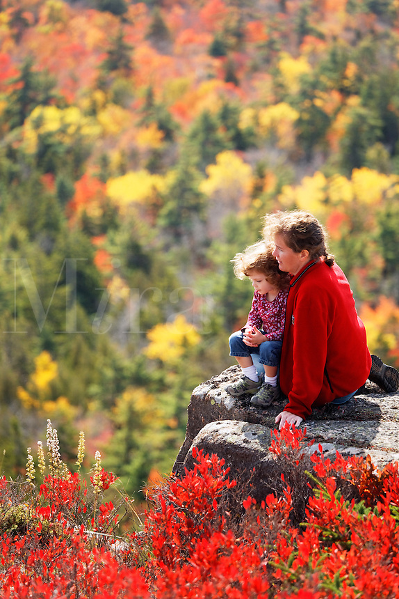 Woman and little girl enjoying fall colored landscape, Mount Desert Island, Acadia National Park, near Bar Harbor, Maine, USA