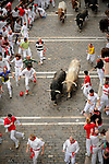 Participants run in front of Fuente Ymbro's bulls during the fifth San Fermin Festival bull run, on July 11, 2012, in Pamplona, northern Spain. The festival is a symbol of Spanish culture that attracts thousands of tourists to watch the bull runs despite heavy condemnation from animal rights groups. (c) Pedro ARMESTRE