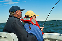 Senior man teacing grand daughter to fish.
