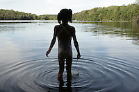 Woodford, VT, USA - August 23, 2008: Young girl holding a fish net watches swimmers in a pond atop the Green Mountains of Vermont.
