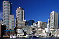 .Boston Harbor Skyline, day. Rowes Wharf,  Boston Harbor Hotel (center with arch). Customs house tower (right). Financial district high-rise buildings (rear) . Massachusetts.Boston skyline day blue sky water architecture  business.Rowes Wharf harbor hotel financial buildings commuter sightseeing boats Massachusetts
