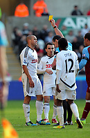 Pictured: Jazz Richards of Swansea (L) sees a yellow card from referee Neil Swarbrick. Sunday 27 November 2011<br />