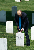 "United States President Donald J. Trump places a flag at a gravesite during the ""Flags-In' ceremony ahead of Memorial Day at Arlington National Cemetery, in Arlington, Virginia on May 23, 2019. ""Flags-In"" is an annual event where the 3rd U.S. Infantry Regiment, ""The Old Guard,"" places American flags at every gravesite at Arlington National Cemetery. <br /> Credit: Kevin Dietsch / Pool via CNP"
