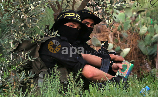 A member of Palestinian militant form the Al-Quds Brigades, the armed wing of the Islamic Jihad movement holds a copy of the Koran, Islam's holiest book as he guards the border between the Gaza Strip and Israel on the Muslim holy fasting month of Ramadan on June 17, 2017. Ramadan is sacred to Muslims because it is during that month that tradition says the Koran was revealed to the Prophet Mohammed. The fast is one of the five main religious obligations under Islam. More than 1.5 billion Muslims around the world will mark the month, during which believers abstain from eating, drinking, smoking and having sex from dawn until sunset. Photo by Dawod Abo Elkass