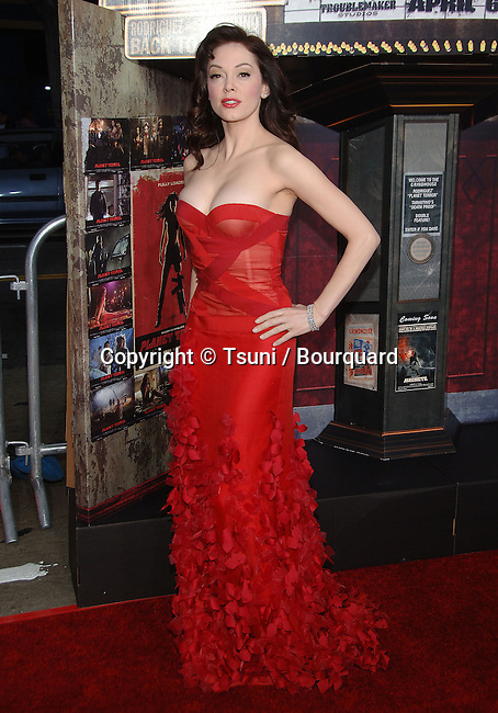 Rose McGowan arriving at the Grindhouse Premiere at the Orpheum Theatre In Los Angeles.<br /> <br /> full length<br /> eye contact<br /> red dress