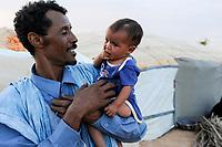 BURKINA FASO Djibo , malische Fluechtlinge, vorwiegend Tuaregs, im Fluechtlingslager Mentao des UN Hilfswerks UNHCR, sie sind vor dem Krieg und islamistischem Terror aus ihrer Heimat in Nordmali geflohen, Tuareg Mann mit seinem Kind aus Timbuktu / BURKINA FASO Djibo, malian refugees, mostly Touaregs, in refugee camp Mentao of UNHCR, they fled due to war and islamist terror in Northern Mali , Tuareg with his child  from Tombouctou