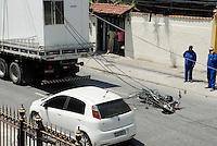 RIO DE JANEIRO, RJ, 04.11.2014 - ACIDENTE TRANSITO - CAMINHÃO E MOTO - Acidente envolvendo um caminhão conteiner que arracou a fiação de uma rua, um motociclista acabou se enroscando no fio e sofrendo queda, na estrada do Bananal em Jacarepagua regiao oeste do Rio de Janeiro , nesta terça-feira, 04. (Foto: Marcus Victorio  / Brazil Photo Press).