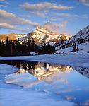 USA, California, Sierra Nevada Mountains. Dana Peak reflecting in a frozen lake.