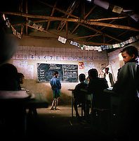An English lesson in Chimbiri school. The signs on the wall are inspired by teaching methods introduced by Voluntary Service Overseas (VSO) volunteers. The same teacher teaches both the morning and afternoon classes for the younger and older pupils respectively, which each contain 54 children...