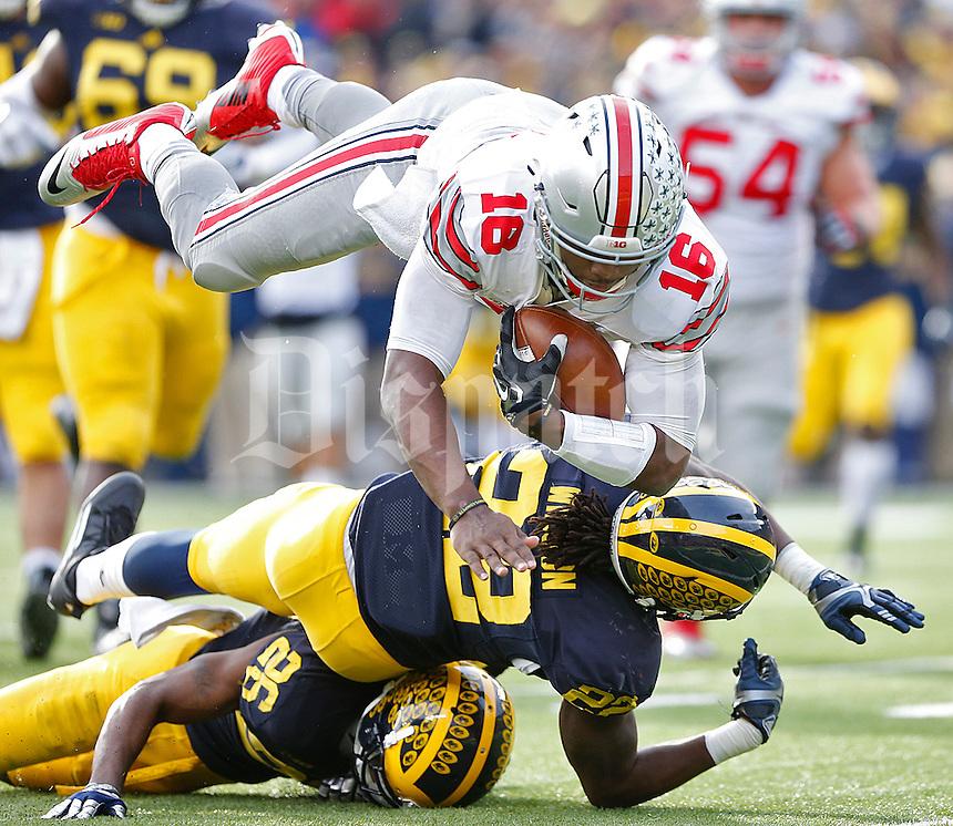 Ohio State Buckeyes quarterback J.T. Barrett (16) flies over Michigan Wolverines safety Jarrod Wilson (22) and Michigan Wolverines cornerback Jourdan Lewis (26) to score a third quarter TD at Michigan Stadium on November 28, 2015. (Chris Russell/Dispatch Photo)