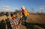 """A Palestinian protester holds up a doll wearing a mask depicting US President Donald Trump's face covered with blood and a shirt with an Arabic slogan reading """"Continuing in spite of Trump"""", during clashes with Israeli troops in tents protest where Palestinians demand the right to return to their homeland at the Israel-Gaza border, in east of Gaza city on September 7, 2018. Photo by Atia Darwish"""