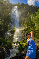 A local woman takes in the sun at the foot of cascading Hi'ilawe Falls (or Hi'ilawe Waterfall), Waipi'o Valley, Big Island.