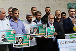 Palestinian members of Hamas legislative council and members of the factions hold banners during a protest to show solidarity with Leader of the northern Islamic Movement Sheikh Raed Salah who is in solitary confinement in Israeli jails in front of Red cross office in Gaza city, on Oct. 27, 2016. Sheikh Salah is currently in Ramon Prison in the Negev and is spending a nine-month prison term. Photo by Yasser Qudih
