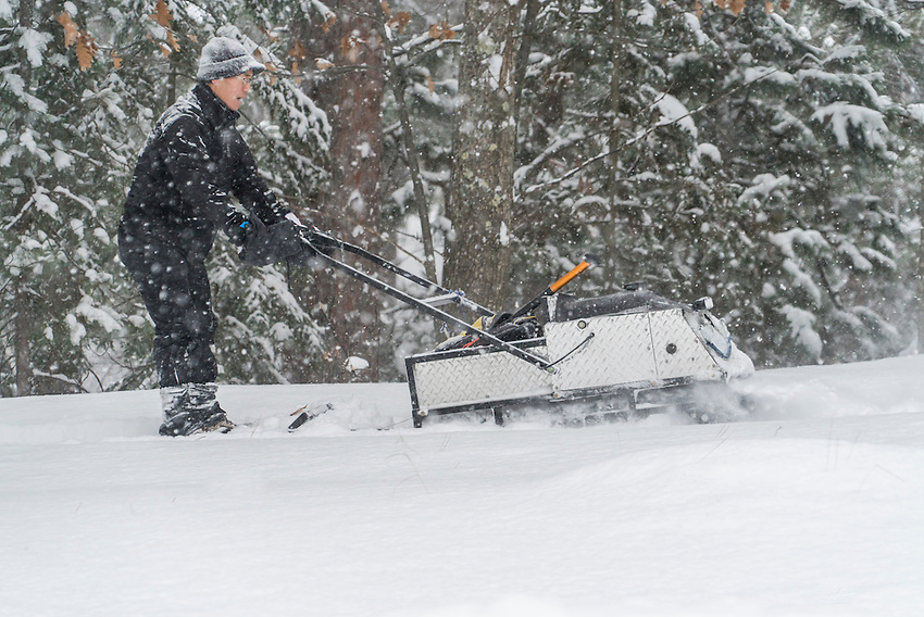 A volunteer with the Noquemanon Trails Network uses a tracksled to groom winter singletrack in Marquette, Michigan.