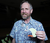 New York, NY, USA - June 24, 2011: Bernie Peyton, Origami designer at the OrigamiUSA Convention in New York City holding one of his creations, a leaf cutter ant.