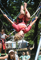 NWA Democrat-Gazette/DAVID GOTTSCHALK  Annalyse Silvey, 8, flips upside down Tuesday, June 5, 2018, as she takes a turn on the Euro Bungee during the Kanakuk KampOut!  at Mount Sequoyah in Fayetteville. The camp offers five days of faith-based, day camp activities to children from kindergarten through fifth grade. The activities included a zip line, inflatables as well as worship time and small group time with counselors.