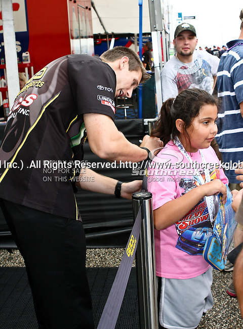 Morgan Lucas #34, driver for Geico Powersport/Lucas Oil's Top Fuel Dragster signs a fans tee shirt durung a rain delay at the O'Reilly Fall Nationals held at the Texas Motorplex in  Ennis, Texas.