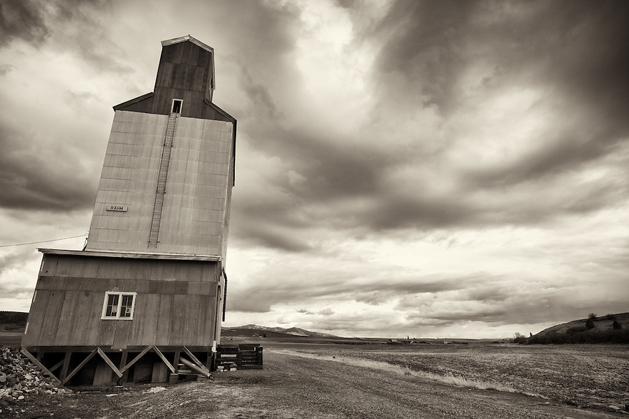 A grain elevator sits along the road, waiting for harvest season.