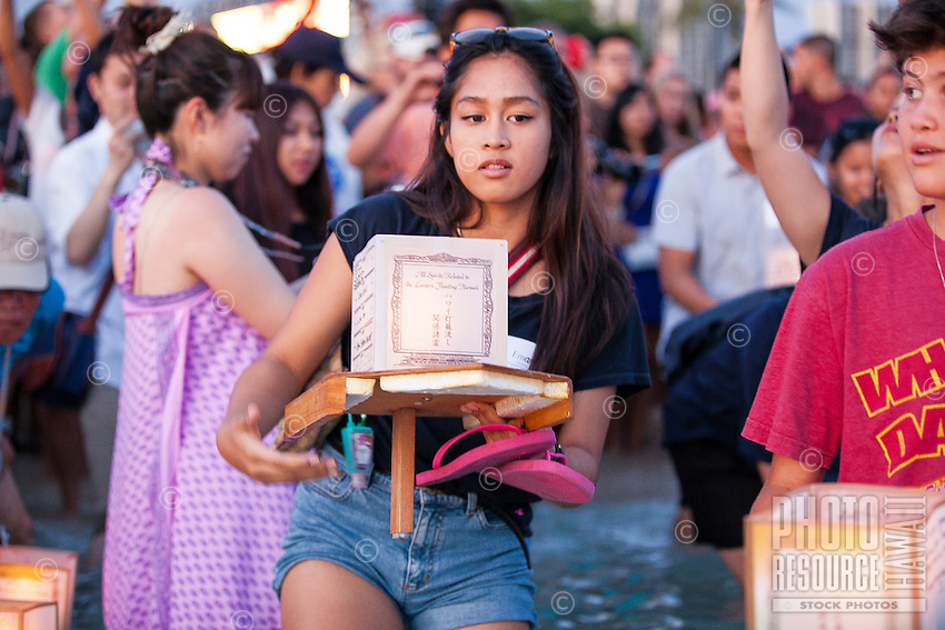 On Memorial Day, a young woman prepares to place a lantern in the ocean at the 15th Annual Lantern Floating Ceremony at Ala Moana Beach Park, Honolulu, O'ahu.