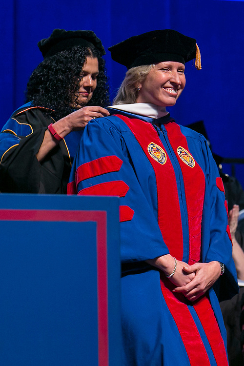 Salma Ghanem, dean of the College of Communication, places a hood on Marty Wilke, broadcast television executive and DePaul alumna, as she receives an honorary degree Sunday, June 11, 2017, during the DePaul University College of Computing and Digital Media and the College of Communication commencement ceremony at the Allstate Arena in Rosemont, IL. (DePaul University/Jamie Moncrief)