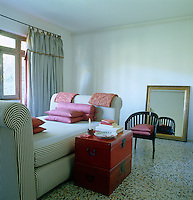In this bedroom mattress ticking has been used for the daybed and the full-length curtains at the window behind