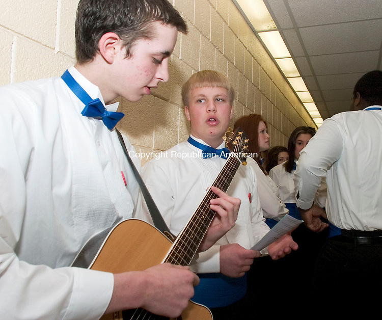 WOODBURY, CT- 27 MARCH 07- 032707JT01- <br /> Matt Russo on guitar and Philip Rice of the Nonnewaug High School Concert Chorus practice in a hallway of the school before performing at the third annual Region 14 regional choral concert on Tuesday night. The concert included choruses from grades 5 through 12 from Bethlehem Elementary School, Mitchell Elementary School, Woodbury Middle School and Nonnewaug High School. Nonnewaug will host a similar concert Wednesday night featuring instrumental bands from the region's schools.<br /> Josalee Thrift Republican-American