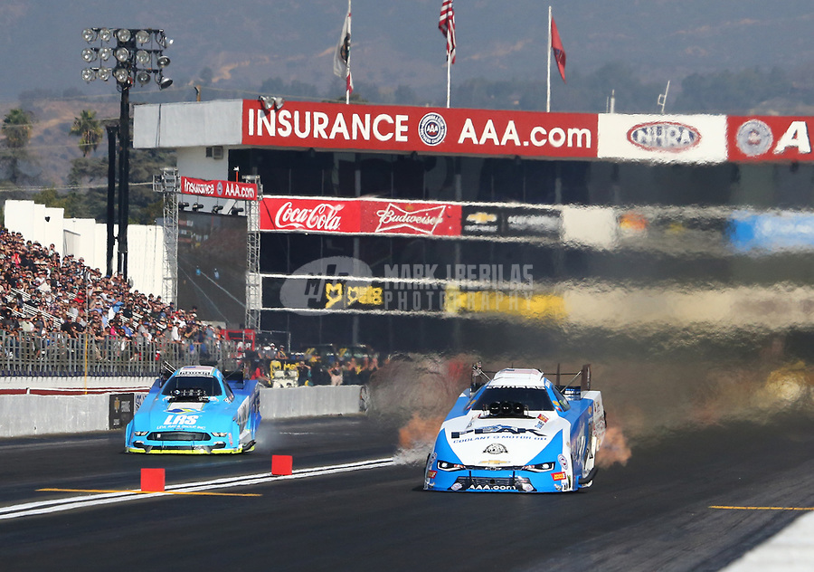 Nov 11, 2018; Pomona, CA, USA; NHRA funny car driver John Force (right) races alongside Tim Wilkerson during the Auto Club Finals at Auto Club Raceway. Mandatory Credit: Mark J. Rebilas-USA TODAY Sports