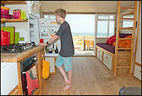 BNPS.co.uk (01202 558833)<br /> Pic: LauraDale/BNPS<br /> <br /> Cam McGregor, whose parents own the beach hut, gets himself a refreshment in the comfortable and spacious interior.<br /> A modest beach hut with no bathroom or mains electricity has gone on the market for a whopping 270,000 pounds - making it the most expensive in Britain.<br /> <br /> The asking price for the tiny wooden shack on Mudeford Spit near Christchurch, Dorset, is the same cost as a plush three-bedroom house in some parts of the country and is as much as a top-of-the-range Ferrari car.<br /> <br /> The 18ft by 12ft hut can sleep up to 12 people - four people on a mezzanine deck, four on two sofa beds and another two on a pull-out bed.<br /> <br /> The huge asking price is because it is just a stones throw away from the water boasting stunning sea views out towards the Isle of Wight and the Needles.<br /> <br /> The current owners are selling the beach hut so that they can move to another one on the same sandy strip with a different view.