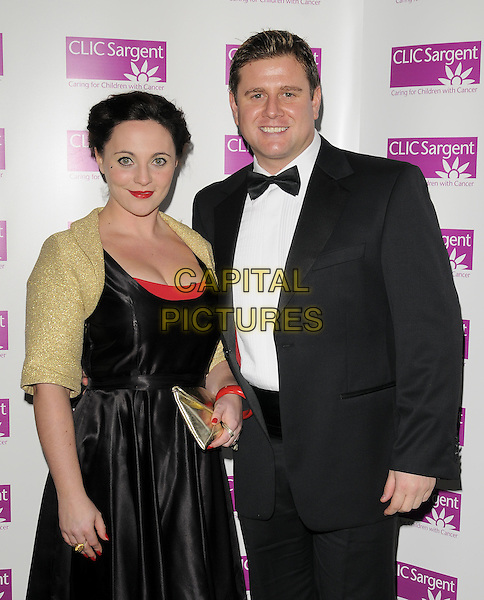 SARAH WILSON & KAI OWEN.The Ruby Ball, The Brewery, Chiswell St., London, England..November 21st, 2008.half length black silk satin dress gold shrug clutch bag tuxedo .CAP/CAN.©Can Nguyen/Capital Pictures.