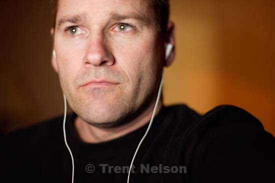 Trent Nelson watching video on computer with headphones at hotel; 3.16.2005<br />