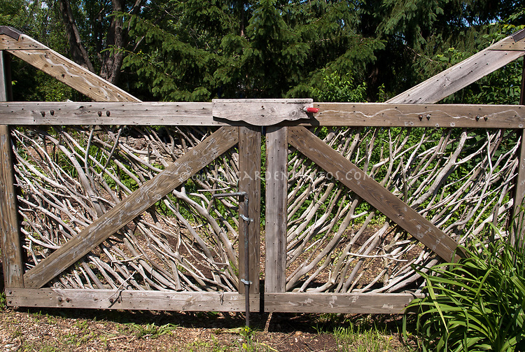 Dress up a wooden fence with a fancy gate to the backyard made from rustic natural tree branches