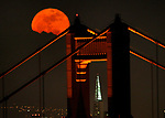 A full moon rises over the Golden Gate Bridge as it the bridge north tower frames the Transamerican Pyramid.