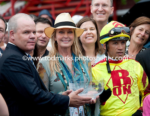 Actress and horse woman Bo Derek presents Turbulent Descent's trainer, Mike Puype and jockey, David Flores, with the Test trophy.