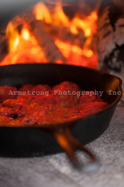 Tomatoes in a cast iron pan, cooked into a sauce inside a wood burning oven. Burning logs in background