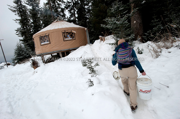 12/11/2009--Seldovia, Alaska, USA..Erin McKittrick, with her son, Katmai, strapped to her back, return with drinking water collected from the well just outside their yurt in Seldovia, Alaska...The yurt is made by Nomad Shelter in Homer, Alaska, and cost about $14,000.  Bretwood Higman ('Hig'), 33 and Erin McKittrick, 30, built it in November, 2008 on land owned by Hig's mother in Seldovia. The yurt is 24' in diameter, the ceiling is over 12' in the middle, 7' around the edge. It has no running water but does have electricity and internet access...McKittrick grew up in Seattle and met Higman, from Seldovia, at Carleton College in 2001.  In June 2007, the couple left Seattle for the Aleutian Islands, traveling 4000 miles solely by human power through some of the most rugged terrain in the world; their adventure has recently been published in a book written by McKittrick with Hig's photographs titled, 'A Long Trek Home: 4,000 Miles by Boot, Raft, and Ski'...Together, the couple also run a small environmental non-profit, Ground Truth Trekking, which uses trekking to explore the complexities of natural resource issues.  The couple lives with their 10 month old son son, Katmai, in Seldovia, Alaska, a 300 person village just off the end of the road system...©2009 Stuart Isett. All rights reserved.