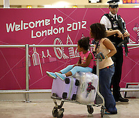 18.07.2012. London, England.  An armed police officer watches a passenger as security measures have been stepped-up at Heathrow airport in London, Britain, 18 July 2012. The London 2012 Olympic Games will start on 27 July 2012.