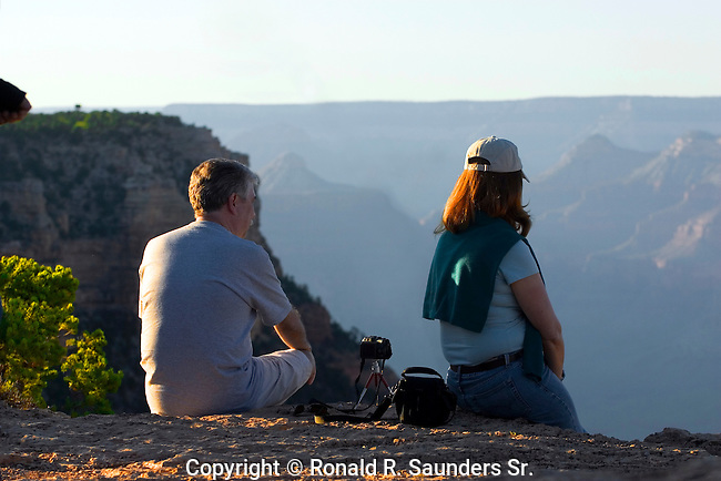 [UNESCO WORLD HERITAGE SITE]<br /> <br /> Couple sit on ledge of Grand Canyon waiting for the sun to set.