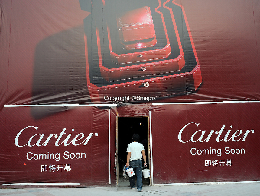 A labour going inside a contruction site of the upcoming Cartier shop in Beijing, China..02 Jul 2008