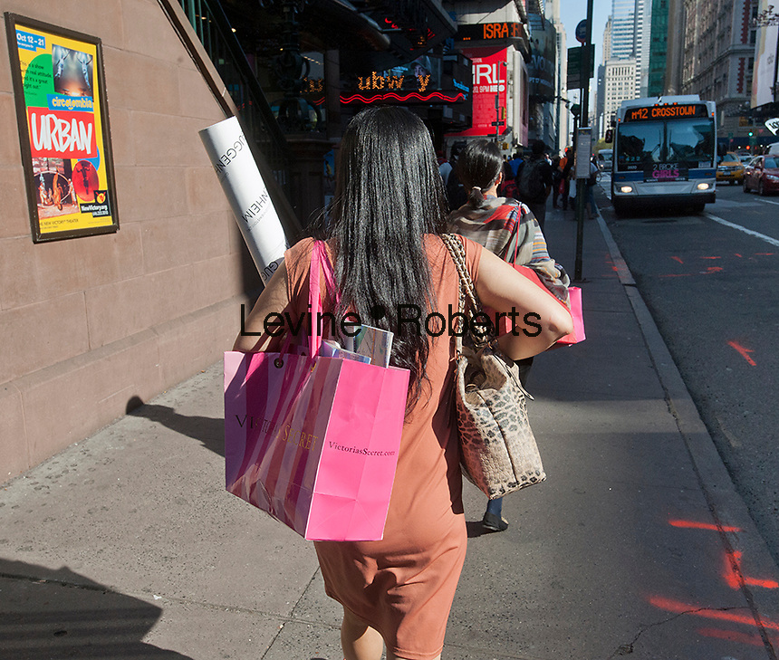 Shoppers in Times Square in New York are seen on Friday, October 5, 2012 carrying their purchases from Victoria's Secret in the company's distinctive shopping bags. (© Richard B. Levine)