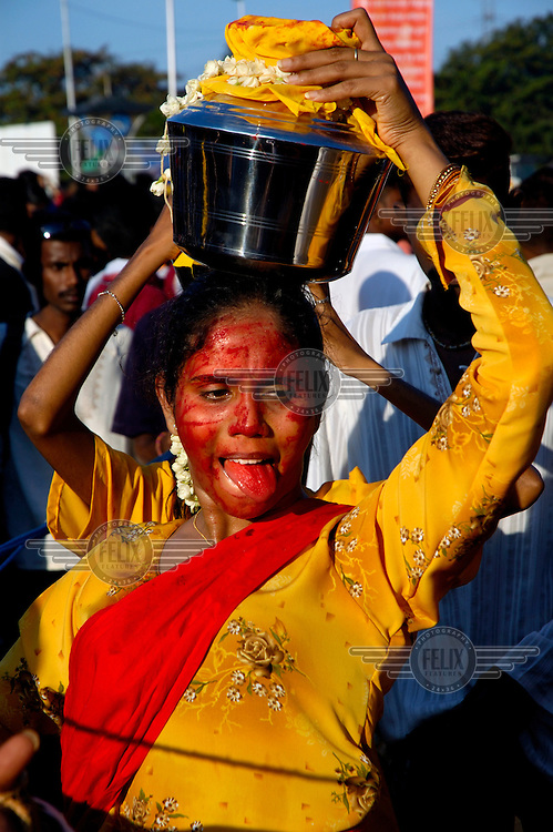 An ethnic Tamil woman carries a pot of milk as an offering along a pilgrimage trail during the annual Tamil Hindu Thaipusam festival of penance and thanksgiving.  Her face is covered in red powder which symbolises her devotion to Hindu Lord Murugan, whose birth and triumph over evil is commemorated during the festival.  Pilgrims engage in various acts of devotion such as carrying burdens, flagellation and body piercing as they take part in a 15-kilometre procession to the Batu Caves. ..