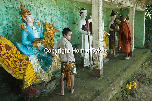 Kyaiktiyo, boy wearing make up called Thanakha cleans nats, which are mysterious spirits and worshiped in Burma in conjunction with Buddhism. Myanmar.
