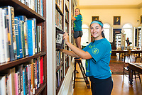 Allison McGovern,'21, right, and Angela Nardi,'21, organize books at the Redwood Library as they participate in the Salve Regina University Exploration Day of Service in Newport.